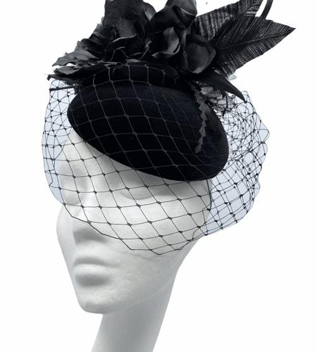 Black velvet headpiece with black veiling along with black flower.