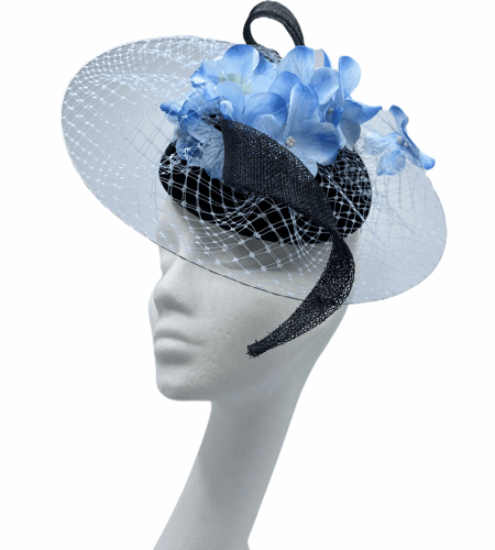 Black velvet headpiece with black sinamay swirl and blue hydrangea on a circular wire, covered in white veiling.