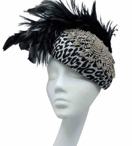 Black and white leopard print hat with large swarovski style detail to top with fab floaty feathers to the back.