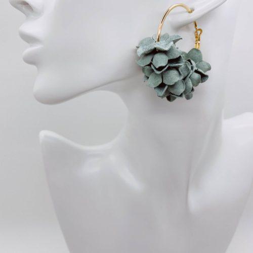 Gold hoop earrings with mint flower detail.