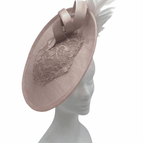 Pink side saucer headpiece with lace centre to the saucer, with pink & cream swirls to the top. It has a cream feather to the opposite side of the saucer on a pink headband.