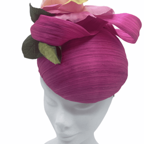 Pink raw silk headpiece with flower detail to top and finished with green leaf.