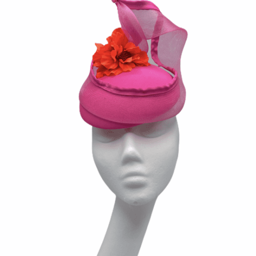 Pink headpiece with pink window swirl and finished with an orange flower to the centre.