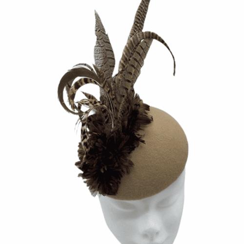 Tan felt feathered headpiece.