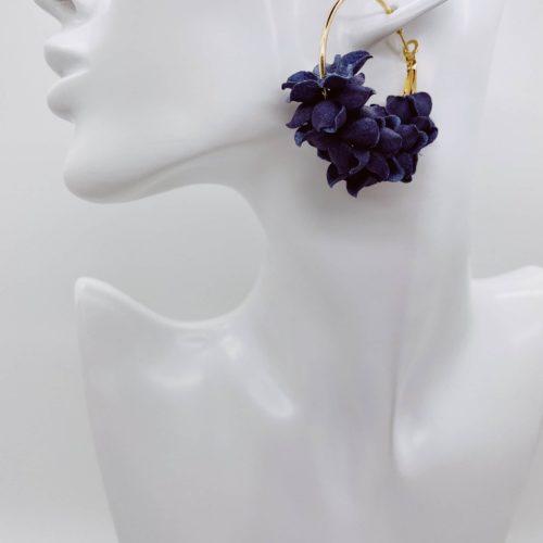 Gold hoop earrings with navy flower detail.