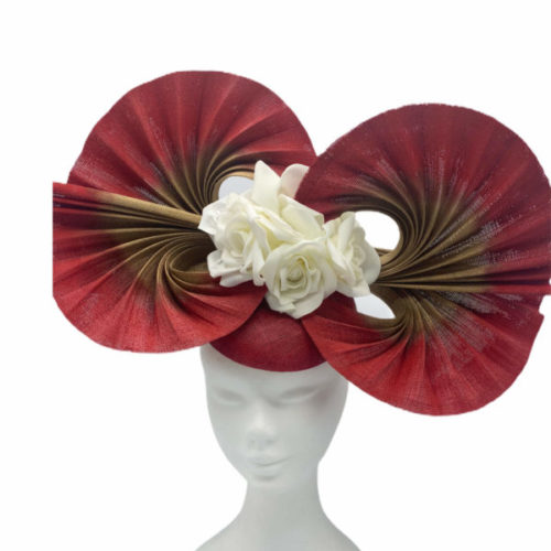 Red headpiece with 2 swirl fans with gold coloured centres and finished with cream flowers to the centre.
