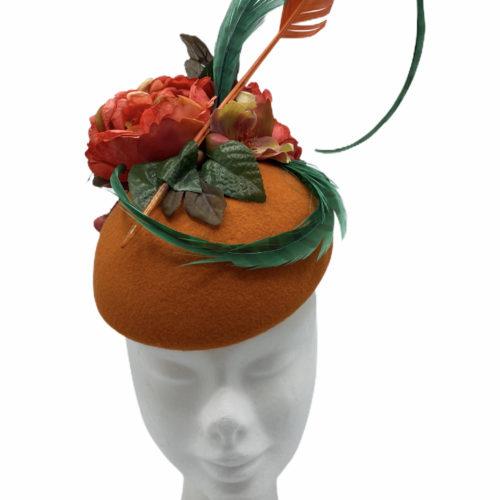 Orange and green felt headpiece with an array of feathers.