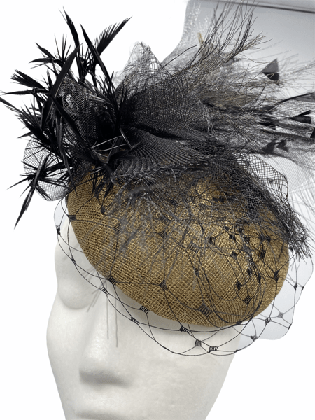 Gold pillbox with veil detail and black feather spray.