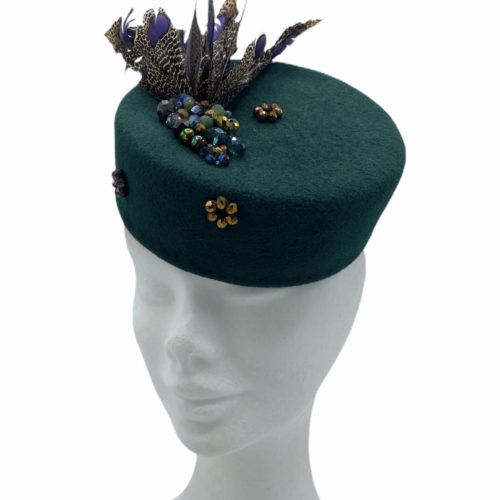 Stunning forest green felt pillbox with an array of beautiful feathers. This headpiece has some beaded detail throughout the base also.