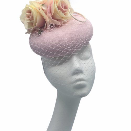 Stunning powder pink pillbox with flowers and veil detail to finish.