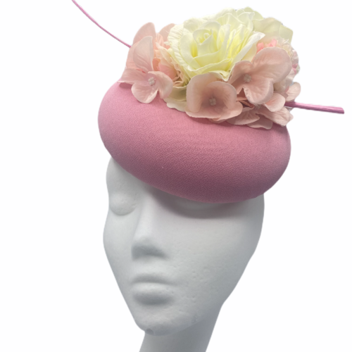 Baby pink pillbox with baby pink and white flowers to the top with a pink quill.