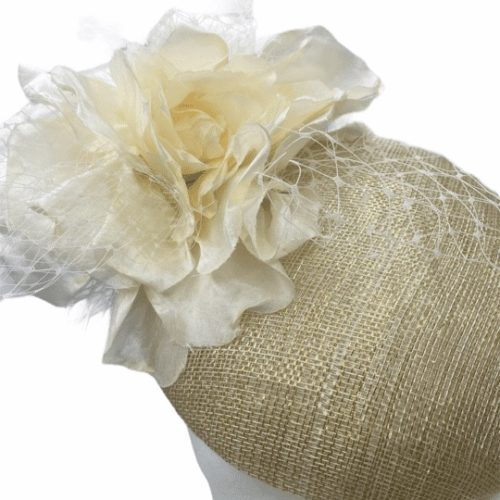 Gold pillbox hat with with cream flower and gold veiling.